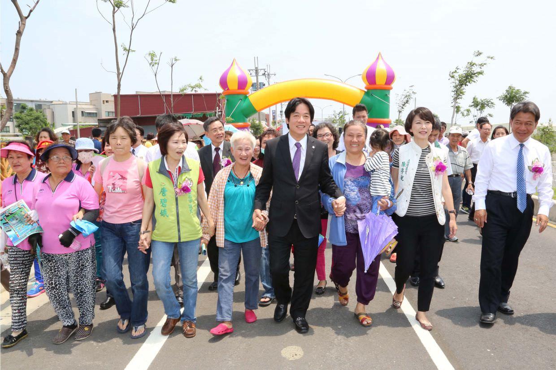 賴清德在鄉親們扶老攜幼參與下,共同步行於完工道路上。(圖片來源:台南市政府/提供)